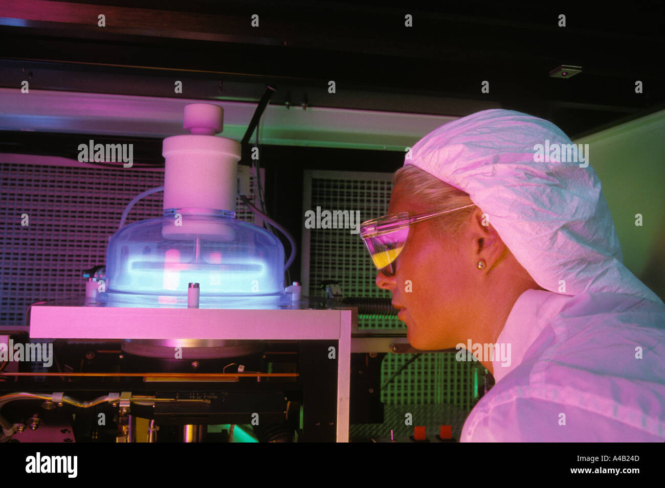 female technician observing silicon wafer undergoing dry plasma etching process in clean room
