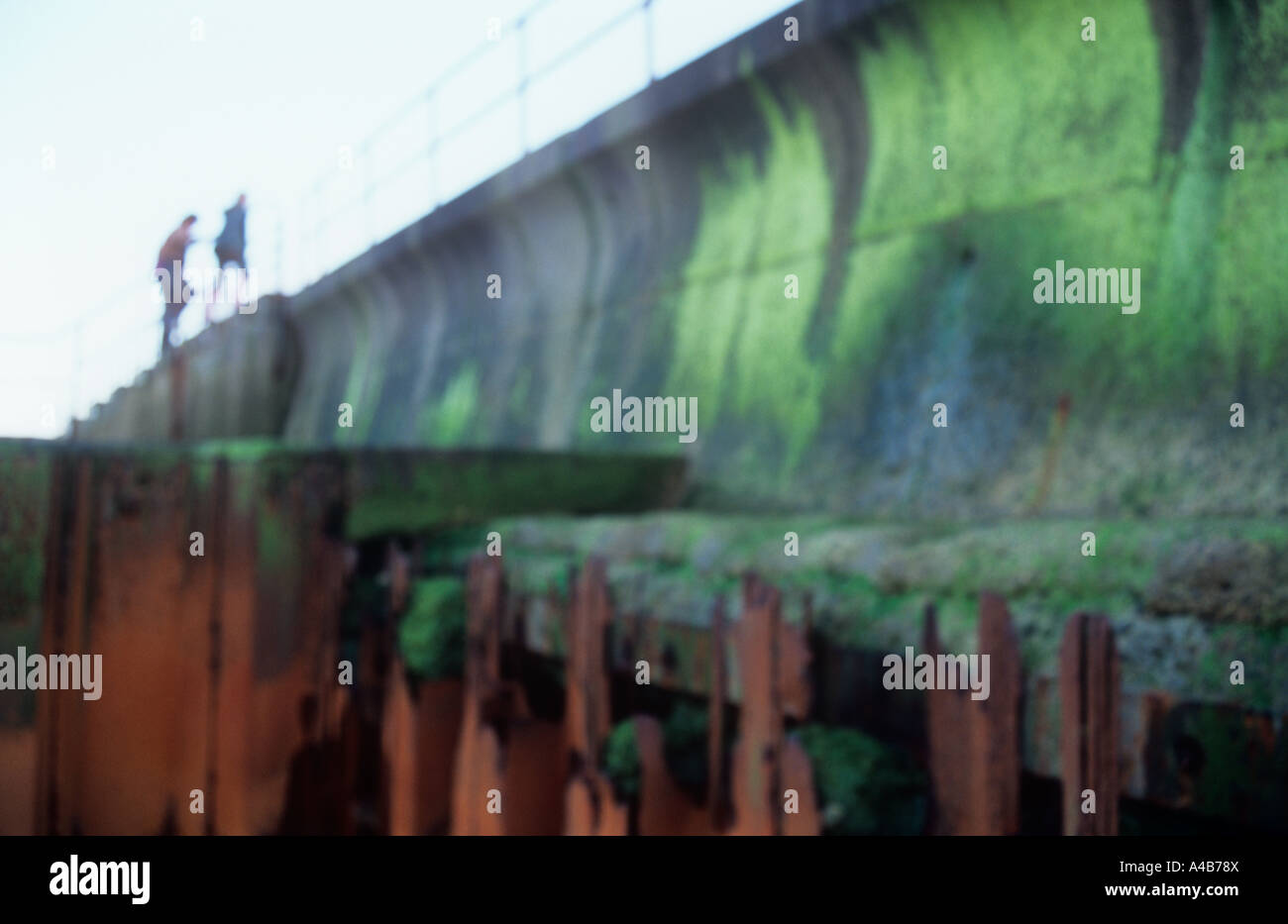 Impressionistic shadowy figures climbing steps of concrete seawall with useless rusted and broken iron sea defence - Stock Image