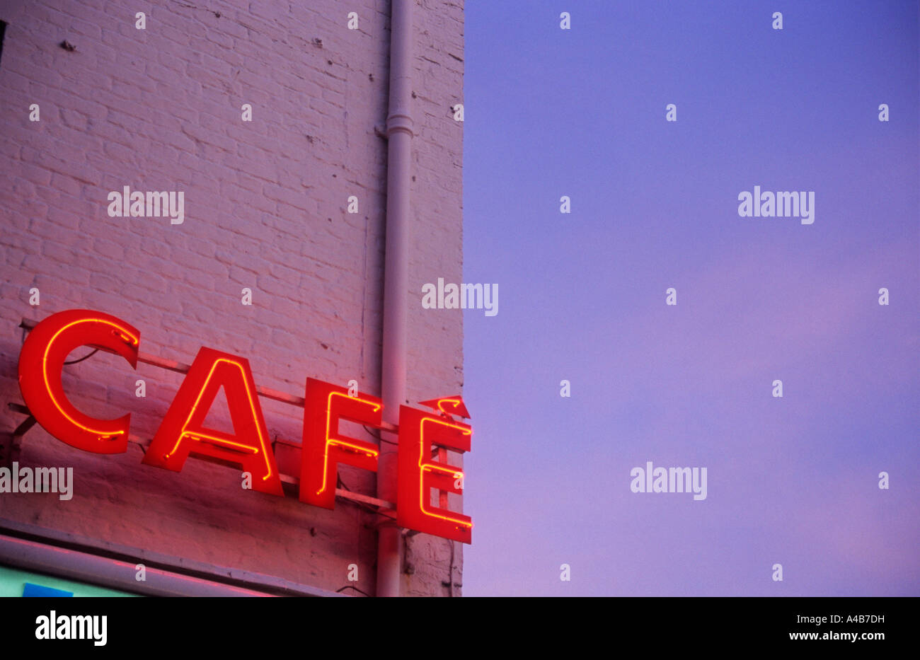 Detail of red neon sign stating CAFE on side of brick wall painted pink and warmly glowing under pink-blue evening - Stock Image