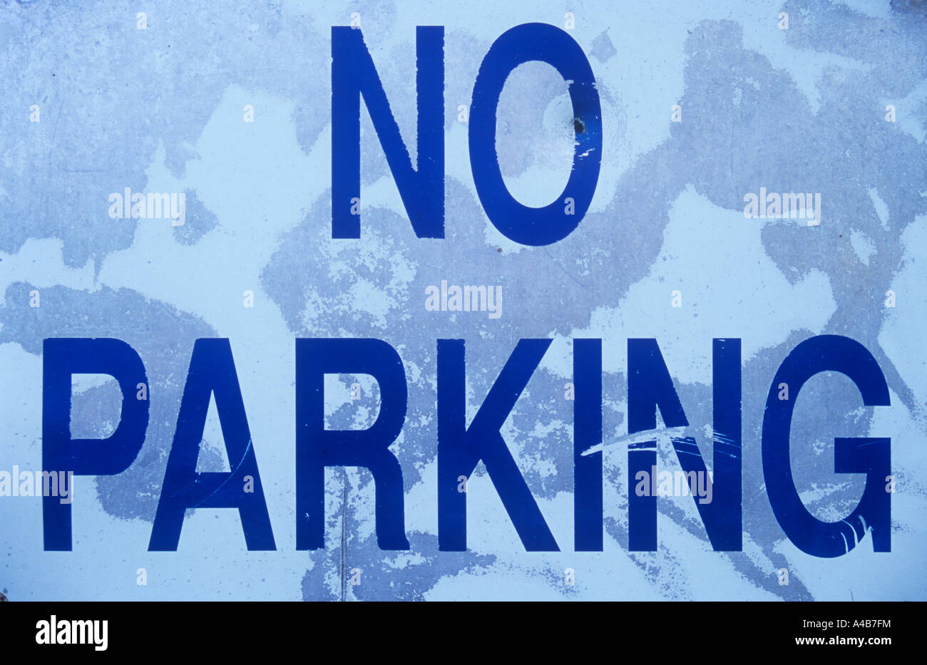 Close up of white blue and grey weathered metal sign stating No parking Stock Photo