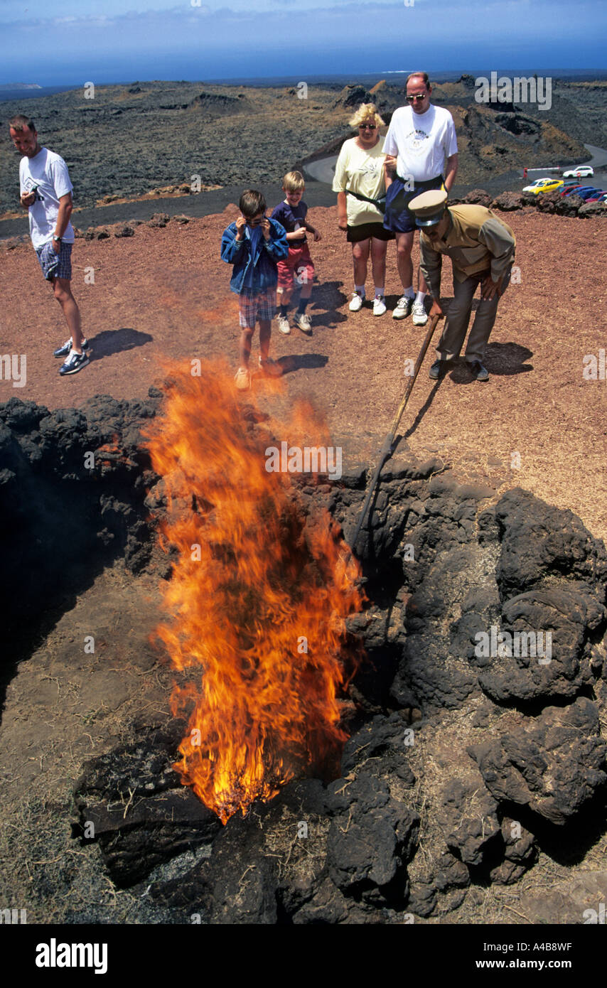 Brushwood ignited by the heat of a volcanic vent in tourist demonstration Timanfaya Lanzarote Canary Islands Spain - Stock Image