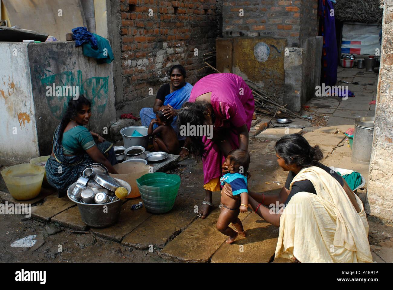 Stock Image of Dalit mother bathing baby boy at community well in the Jagathapuram slum in Chennai Tamil Nadu India - Stock Image