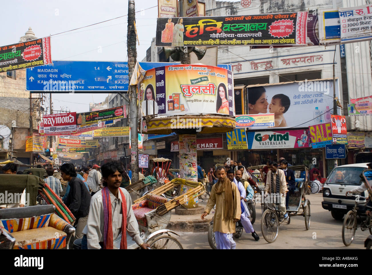 Stock image of crowded street with rickshaws people cars and billboards in Varanasi India - Stock Image