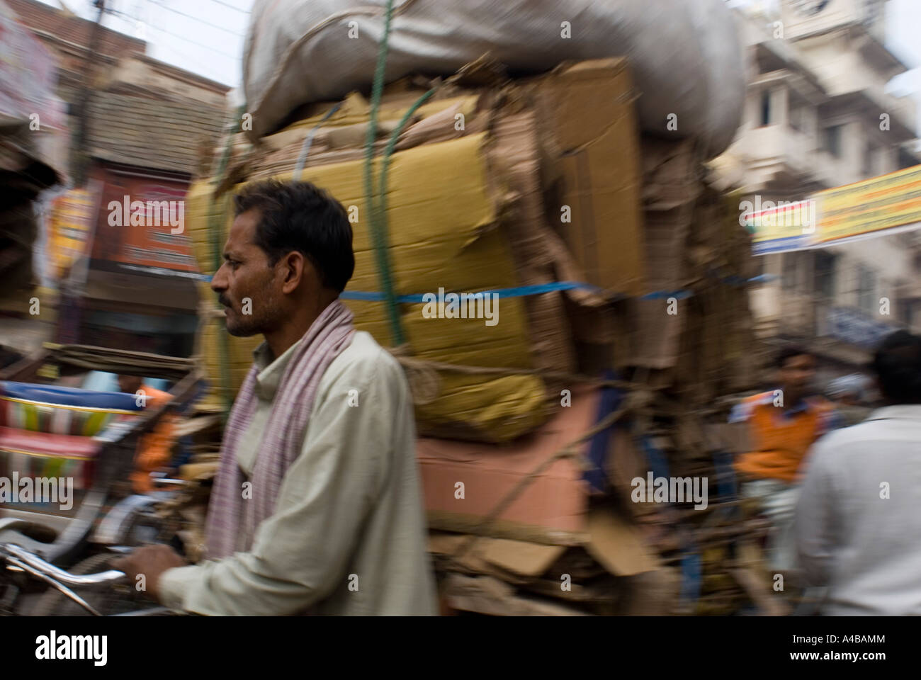 Bicycle rickshaw carrying huge stack of cardboard for recycling in Varanasi - Stock Image