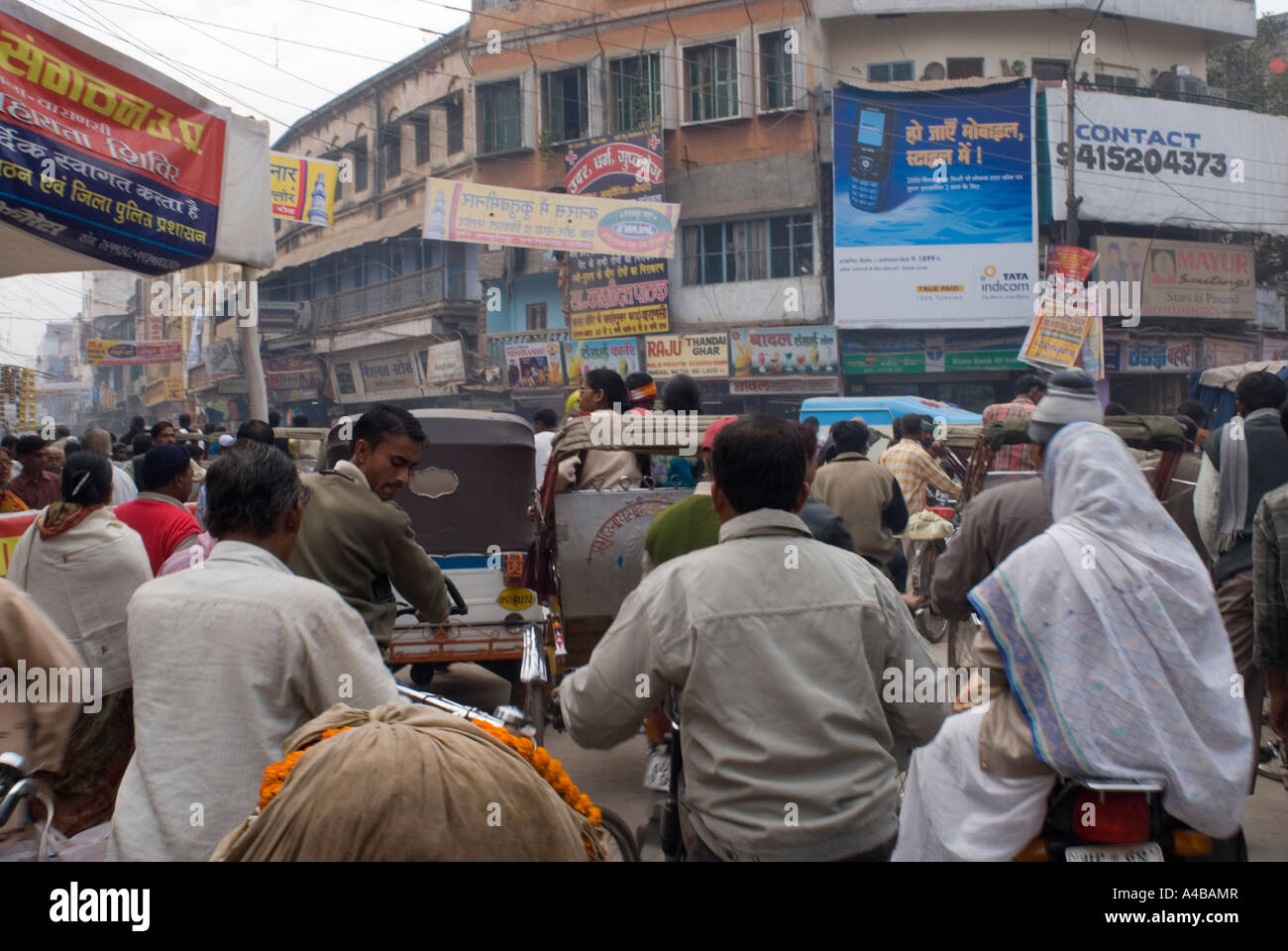 Stock image of crowded street with rickshaws people cars and billboards in Varanasi India in a traffic jam - Stock Image