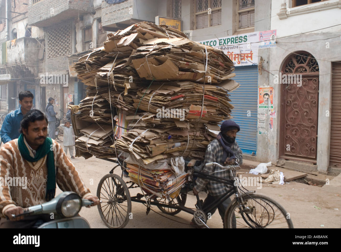 Stock image of crowded street with rickshaw carrying a ton of carton to recycle in Varanasi India - Stock Image