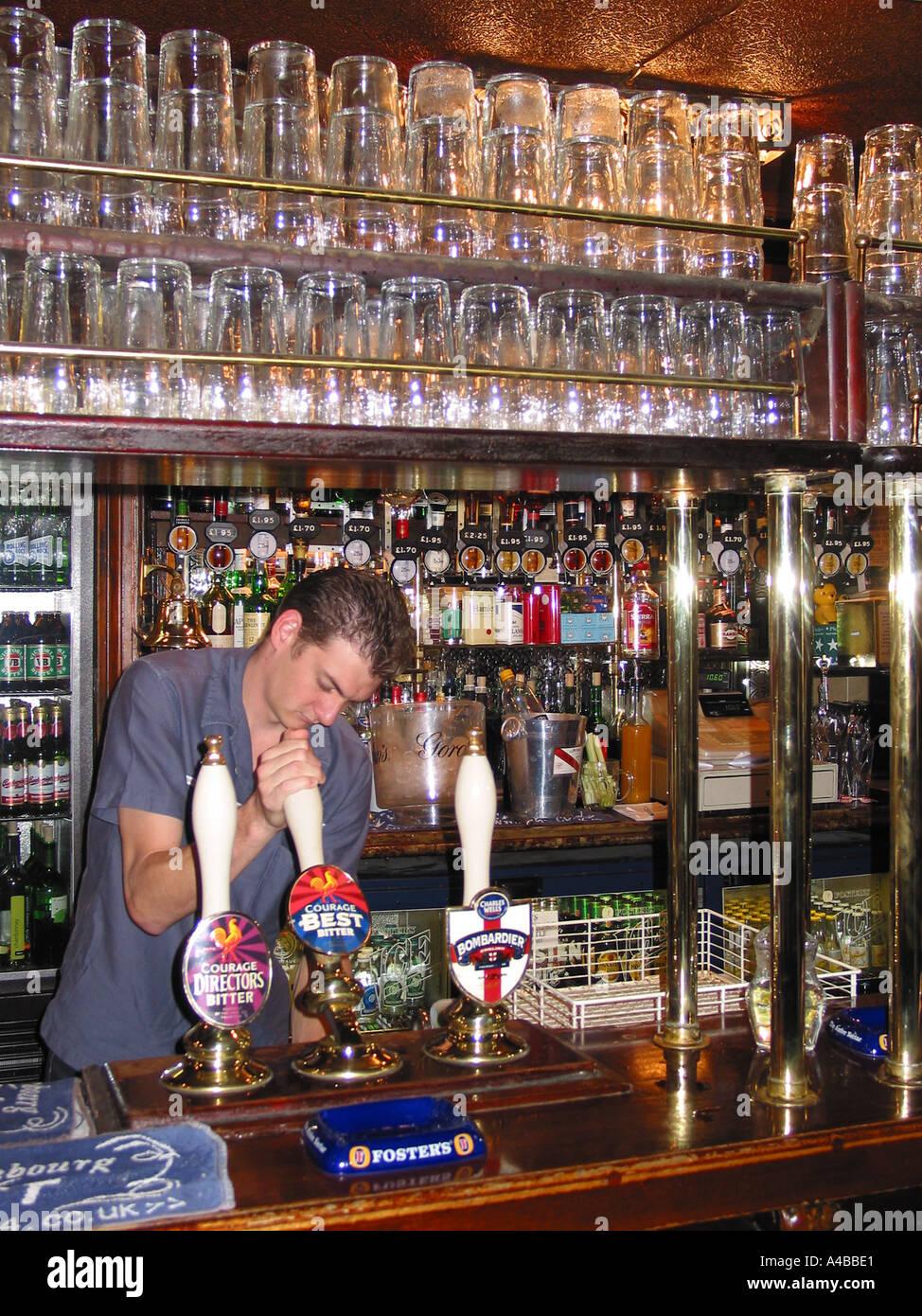 Barman serving Traditional British Pub Scene - Stock Image
