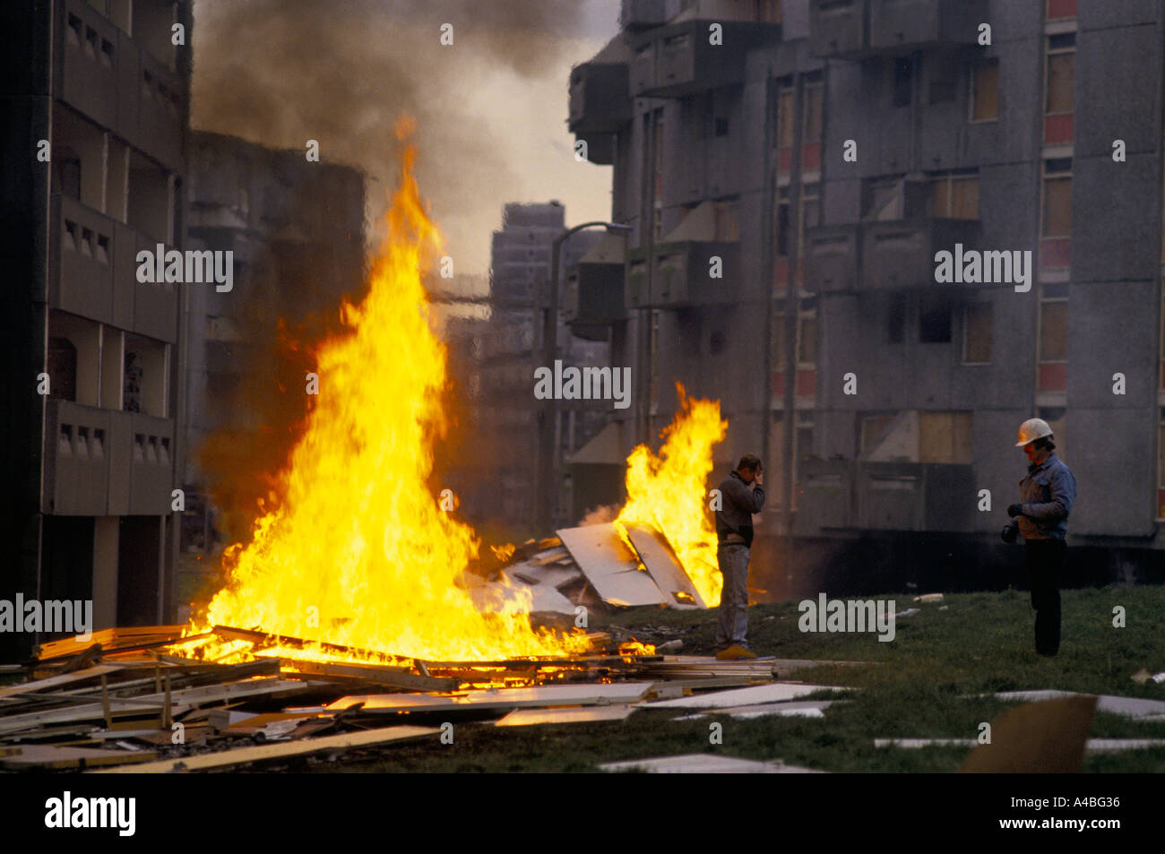 SCRAP PANELS BURNING IN HIGH FLAMES ON GROUND OF HUME CRESCENT. WORKERS OF DEMOLITION IN DESPAIR. HIGH RISE ESTATE. - Stock Image