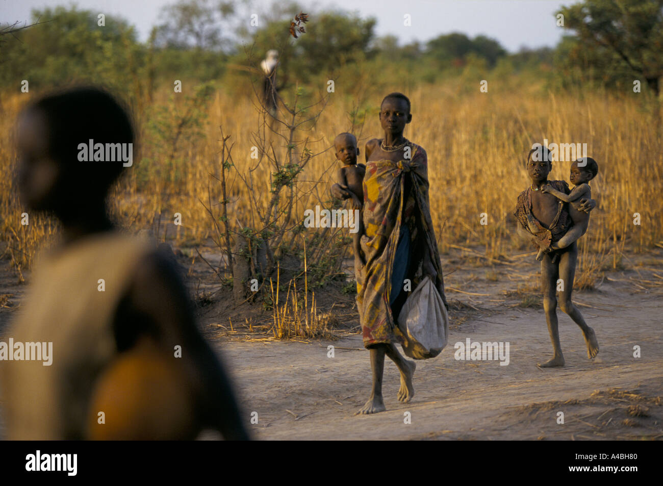 southern sudan ageip village malnourished family mother carrying children walking on road - Stock Image