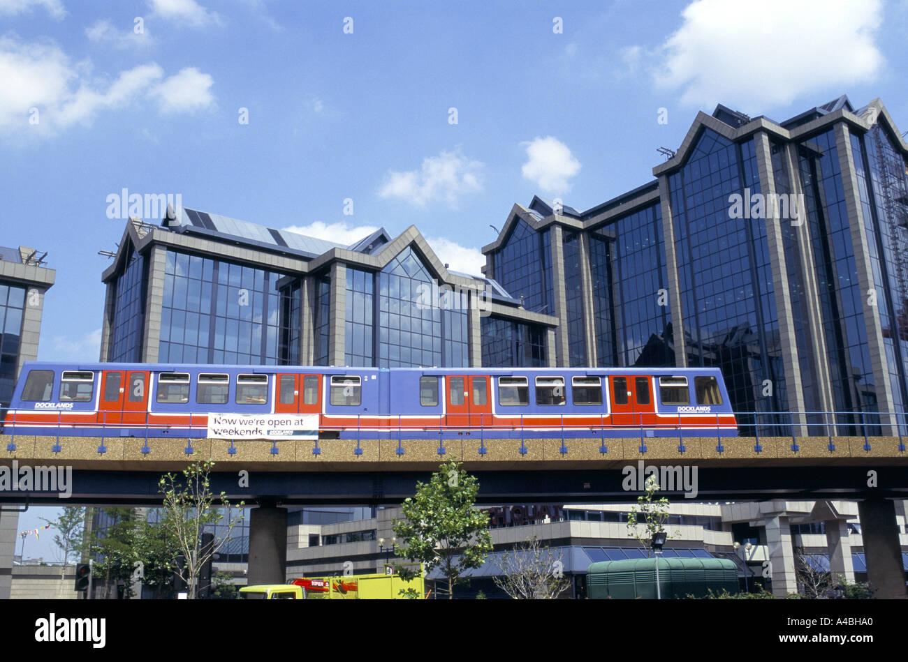 THE DOCKLANDS LIGHT RAILWAY RUNNING ON OVERGROUND TRACK ALONGSIDE  BUSINESS BUILDINGS LONDON, ENGLAND 1999 - Stock Image
