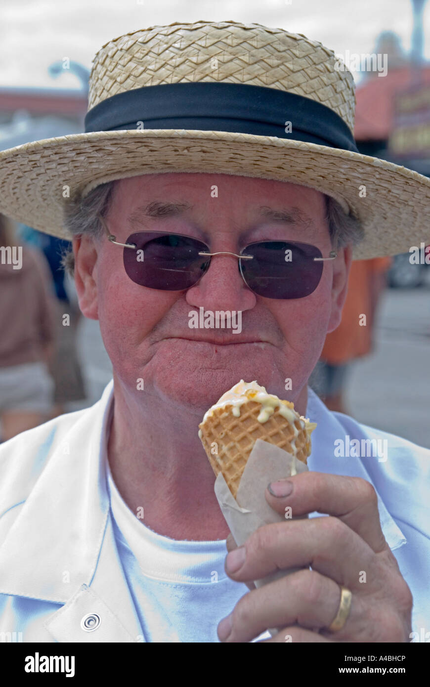 A man in a straw boater hay with an ice cream - Stock Image