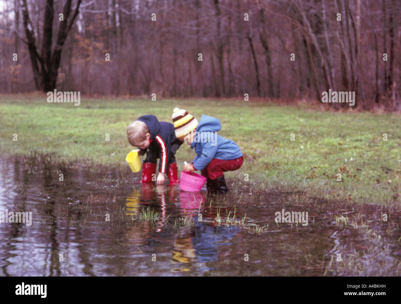 27,091.34100 two boys 3 & 4 years old wading in big rubber boots and cold-weather coats playing in a big water - Stock Image