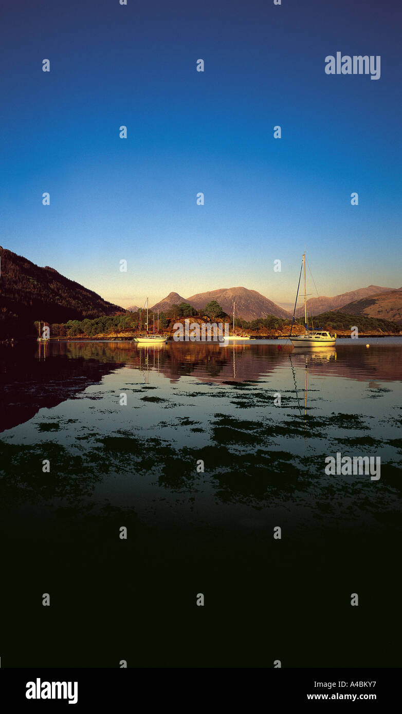 A summer's evening and boats lie peacefully at anchor, Loch Leven. - Stock Image
