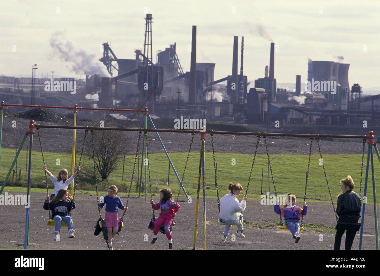 Motherwell, Scotland March 1992. Children  play on swings. Ravenscraig steel works closed in 1992 causing mass unemployment Stock Photo