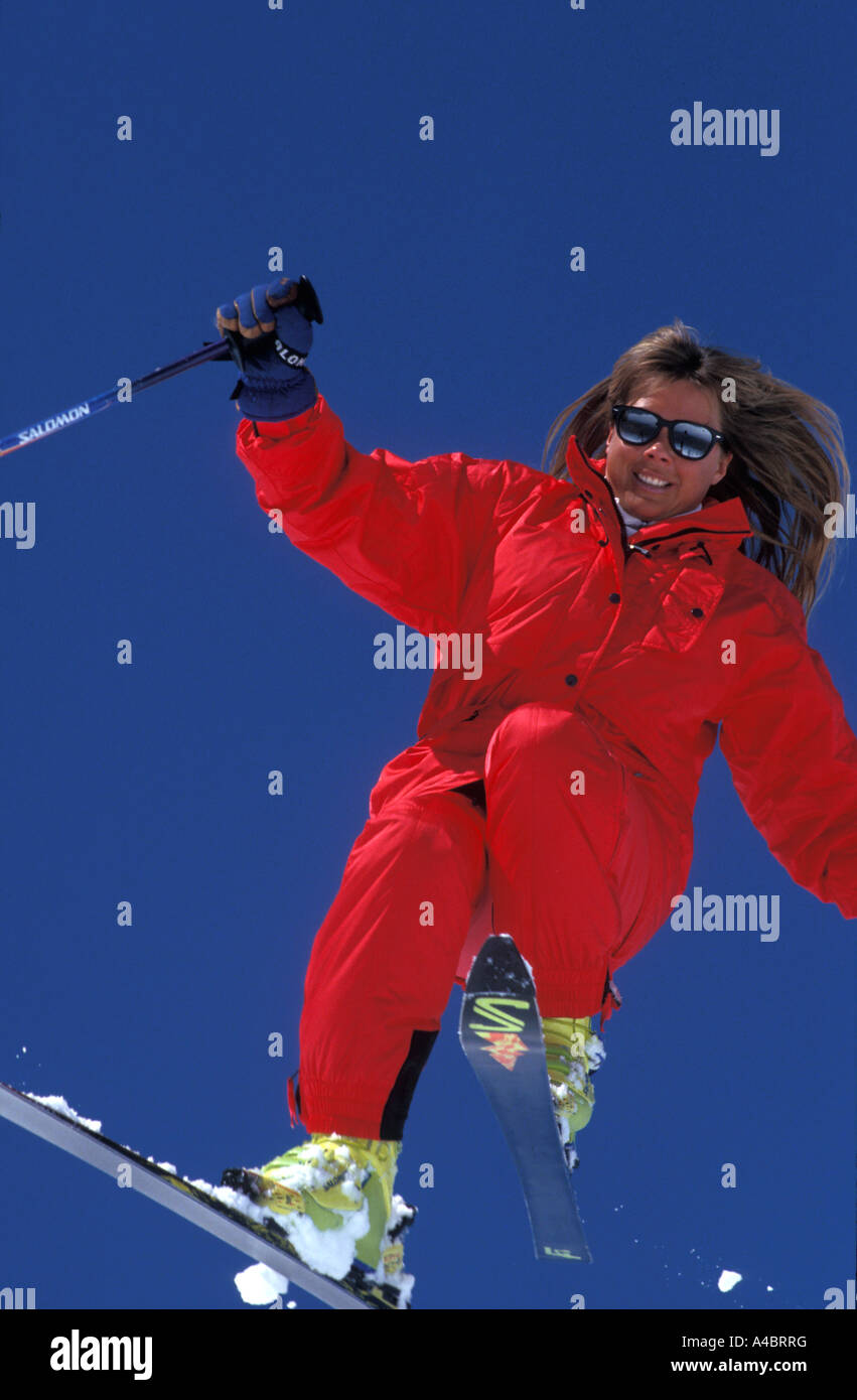 Female skier in a high jump wearing a bright red ski suit and yellow ski boots - Stock Image