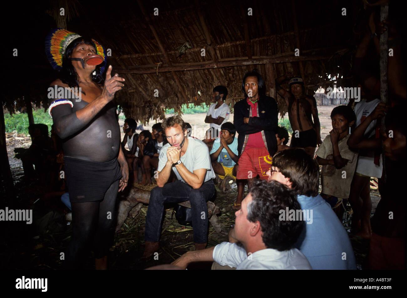Amazon, Brazil. Sting with face paint, Larry Cox listening to Chief Raoni; men's hut, Capoto village, Megranoti Reserve. - Stock Image
