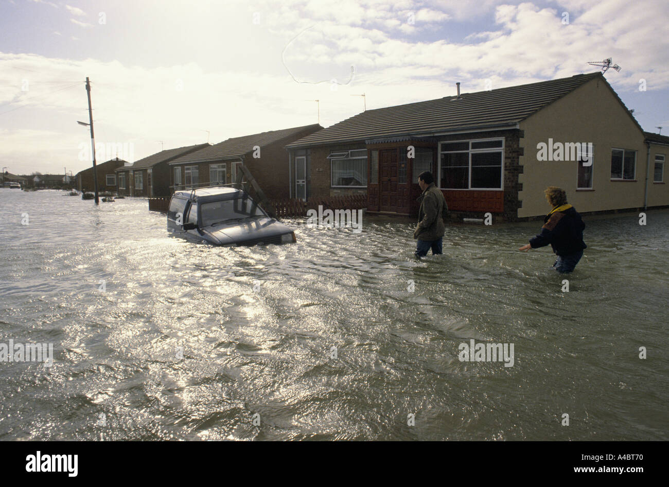 Wading to their waterlogged car after Hurricane winds cause the sea wall at Towyn, North Wales to break, flooding Stock Photo