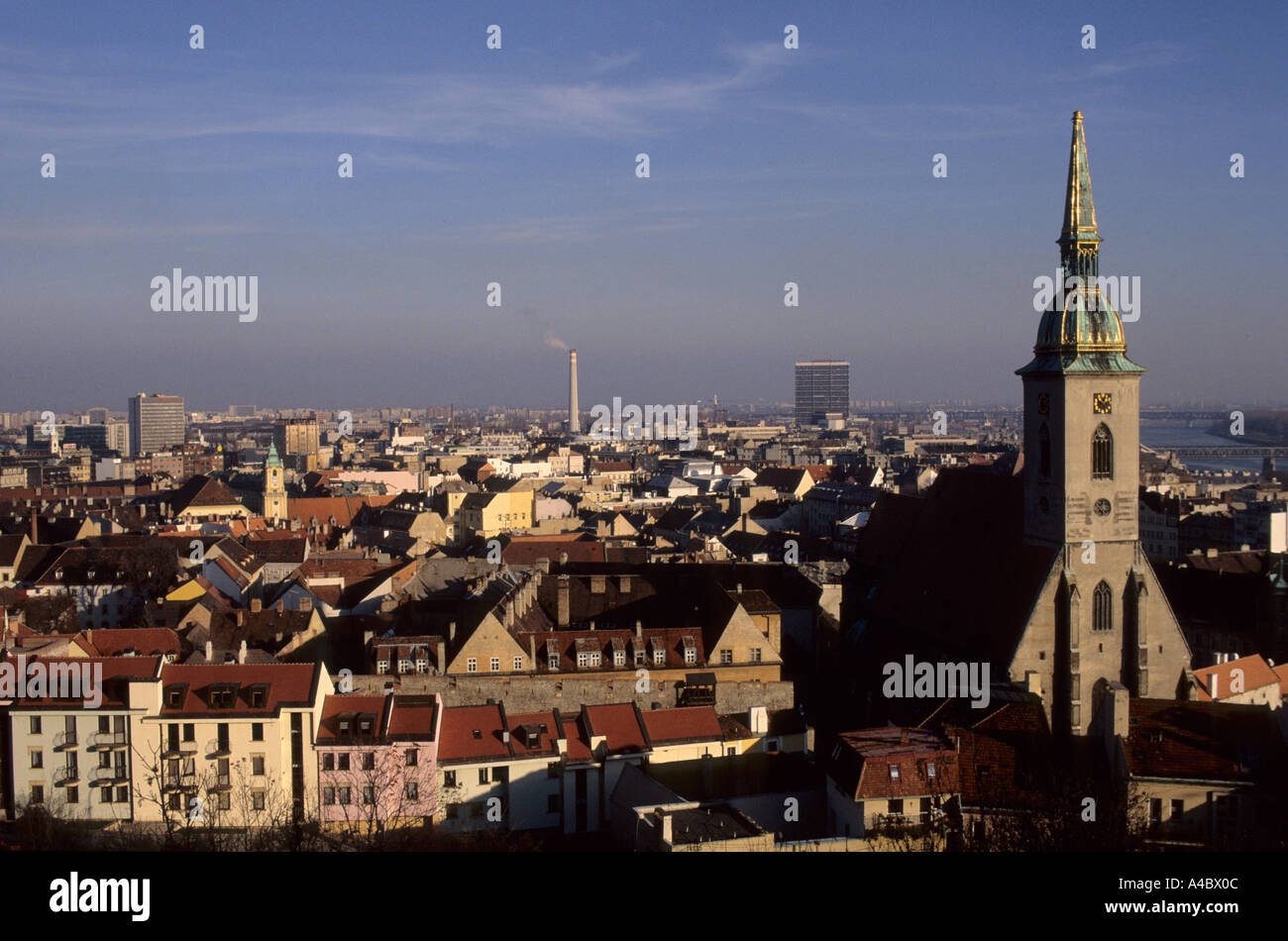 Bratislava, Slovakia. View over the city; St Martin Coronation cathedral church spire; smoking industrial chimney. - Stock Image