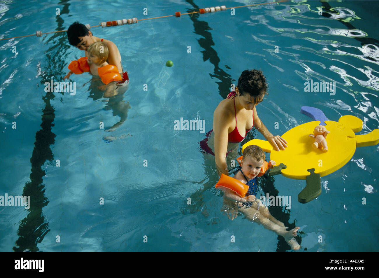 YOUNG CHILDREN, LEARNING TO SWIM, WEARING INFLATABLE ARM-BANDS, ACCOMPANIED BY THEIR MOTHERS IN SWIMMING POOL, - Stock Image