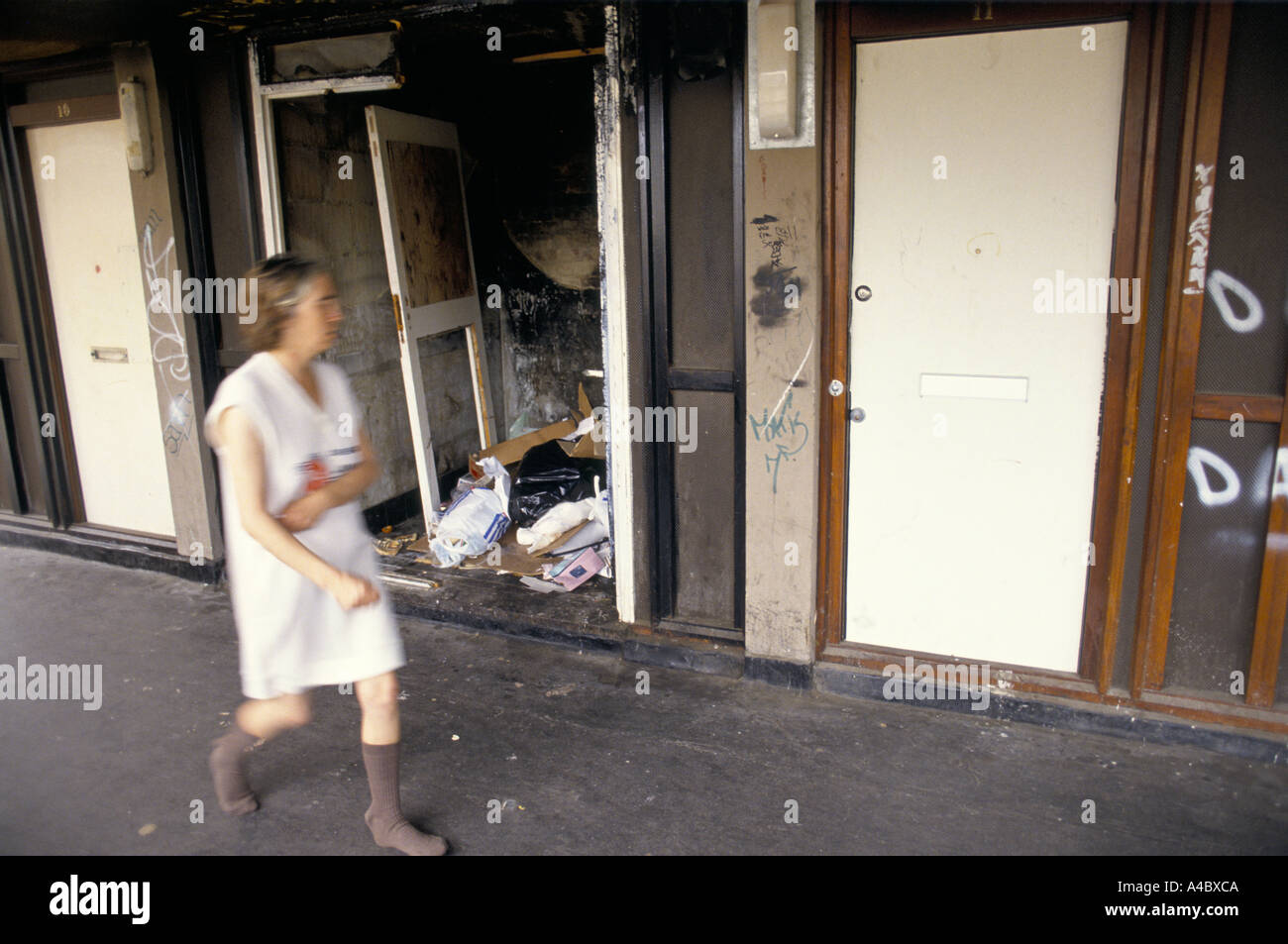 A WOMAN IN PYJAMAS & SOCKS WALKING PASS A DOORWAY OF A DERELICT FLAT LITTERED WITH GARBAGE IN A HOUSING ESTATE - Stock Image