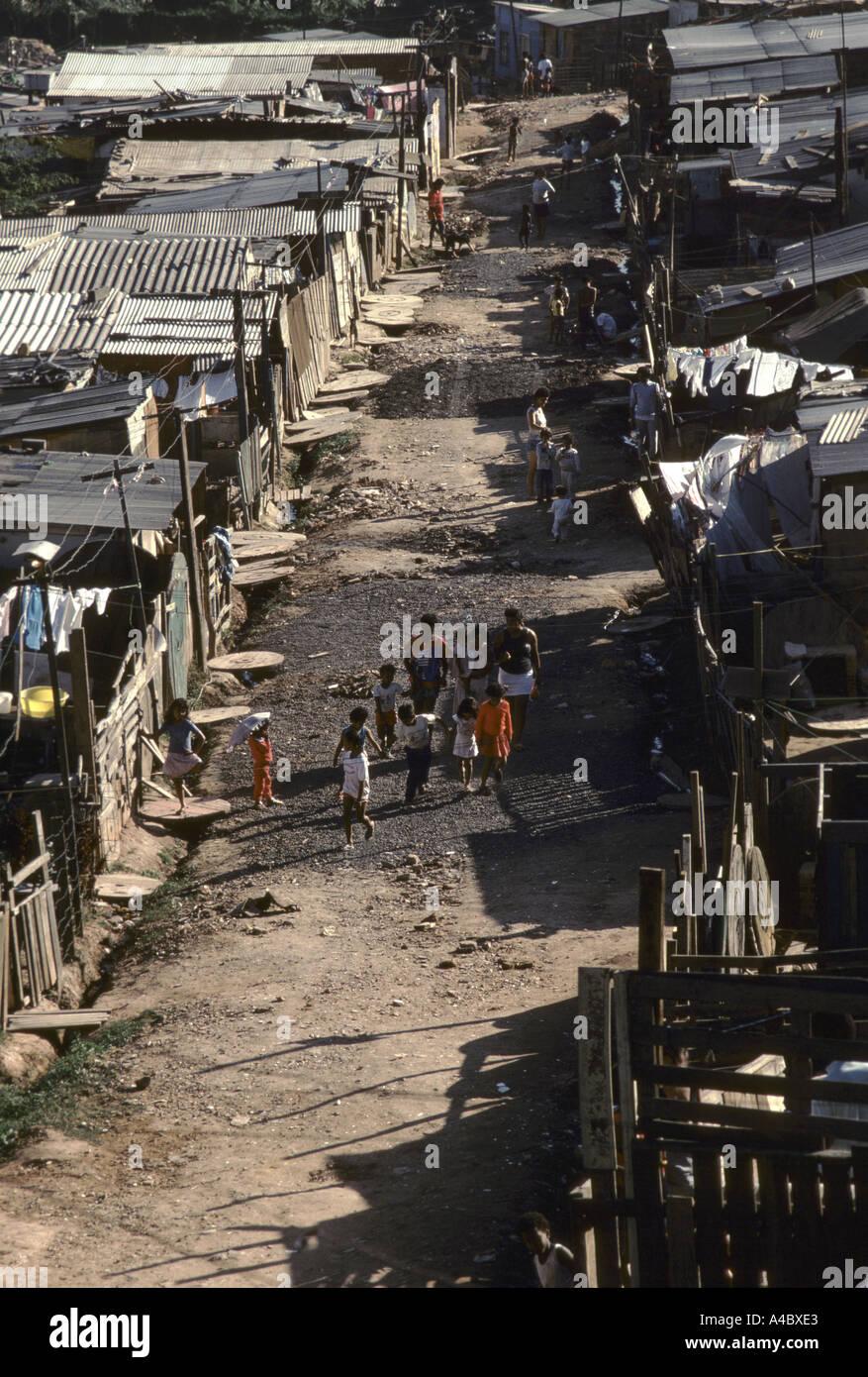 Residents walk along the path between shacks at the Casa Verde land invasion Sao Paulo Brazil - Stock Image