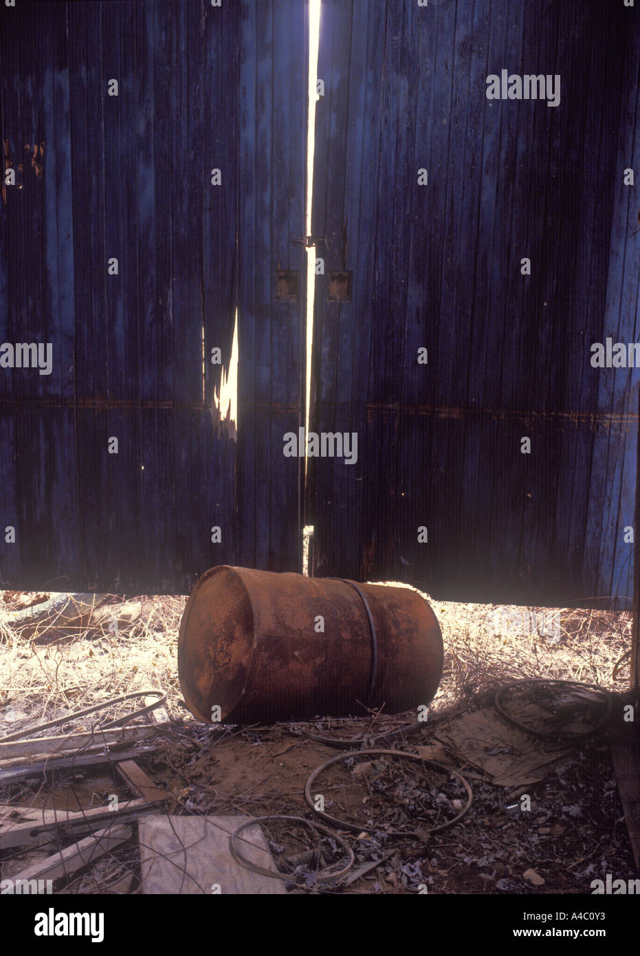 Old Rusty Oil Drum In Ramshackle Shed - Stock Image