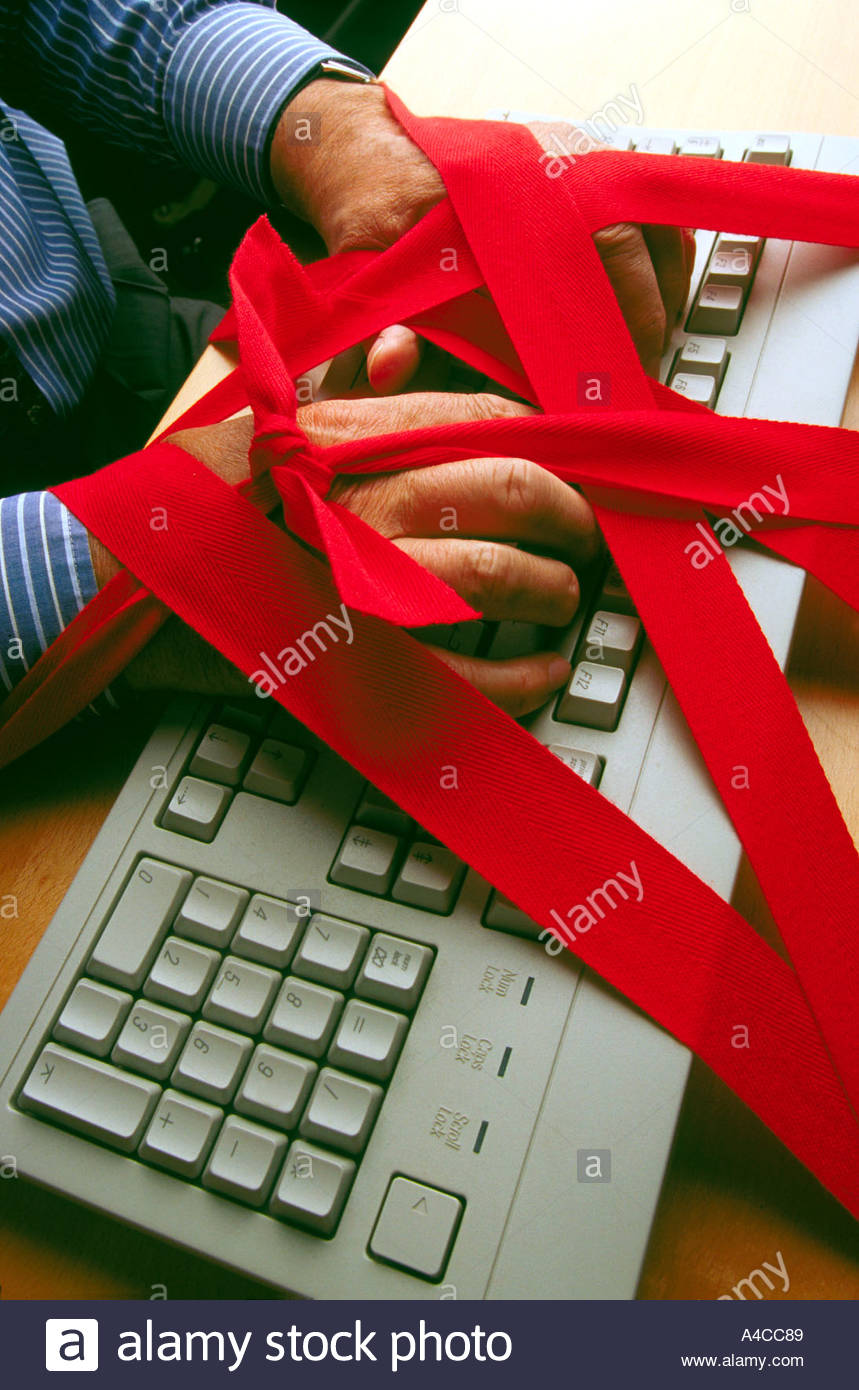 Keyboard and hands tied with red tape - Stock Image
