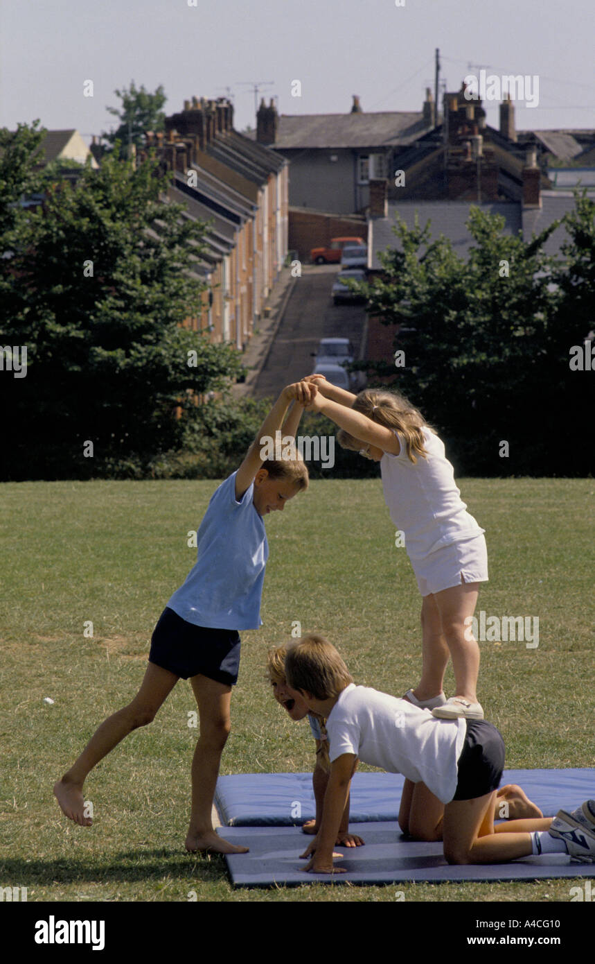 PUPILS DOING EXERCISE ON MAT DURING PHYSICAL EDUCATION LESSON IN PRIMARY SCHOOL - Stock Image