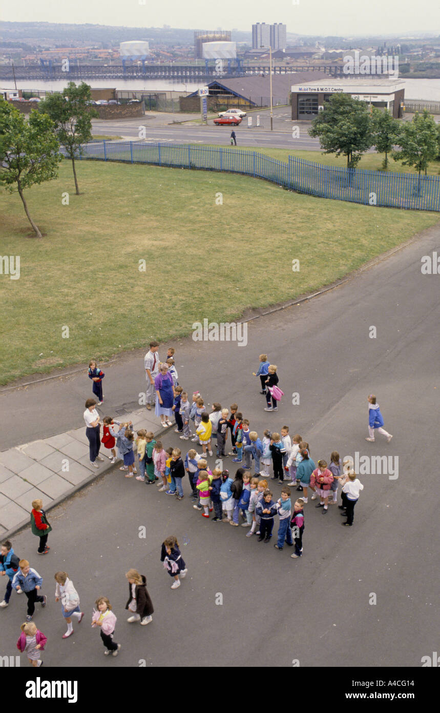 CHILDREN IN A PRIMARY SCHOOL PLAYGROUND LINE UP BEFORE THE BEGINNING OF CLASS. - Stock Image