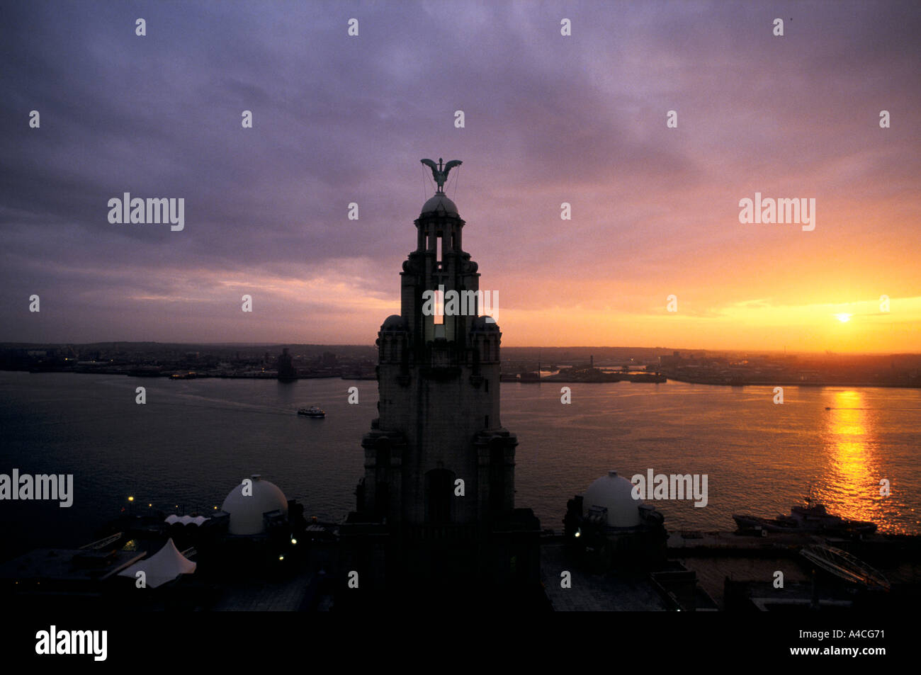 A LIVER BIRD ON TOP OF THE LIVER BUILDING IS SILHOUETTED AGAINST THE SKY AT SUNSET AT THE ALBERT DOCK, LIVERPOOL, ENGLAND - Stock Image