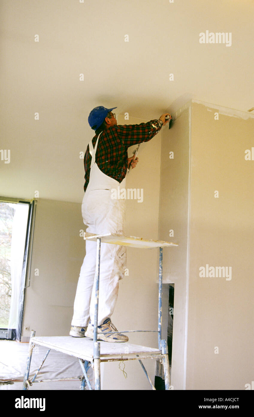 Decorator painting a wall inside a house - Stock Image