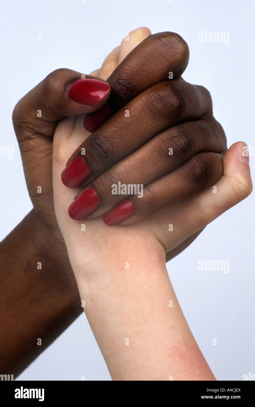 Black and white hands clasped in harmony and friendship - or fighting - Stock Image