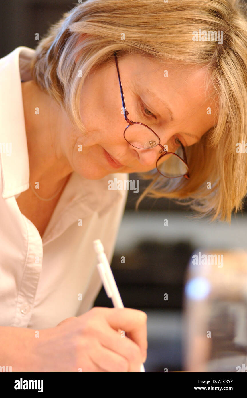 Royalty free photograph of mature British business woman director in meeting writing in London UK - Stock Image