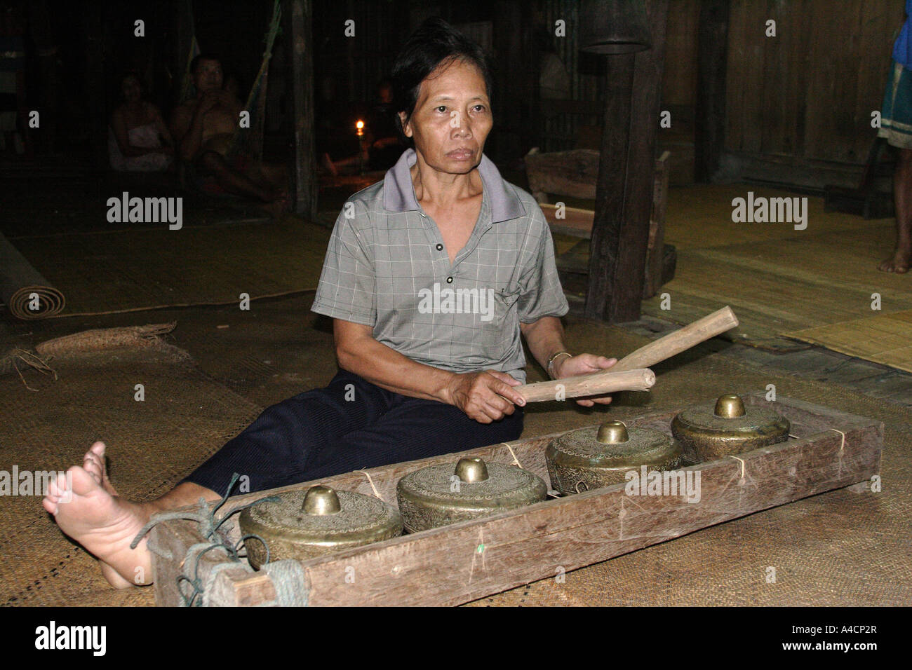 Iban woman playing traditional instrument in Lalang longhouse at Skrang river area, Sarawak Malaysian Borneo - Stock Image