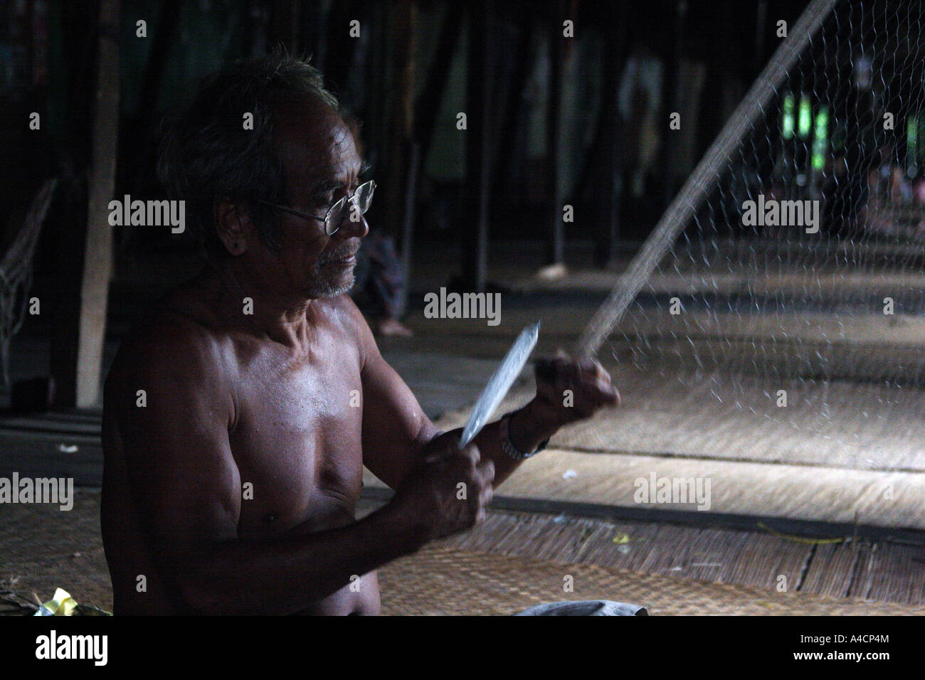 Iban man fix his net in Lalang longhouse at Skrang river area, Sarawak Malaysian Borneo - Stock Image