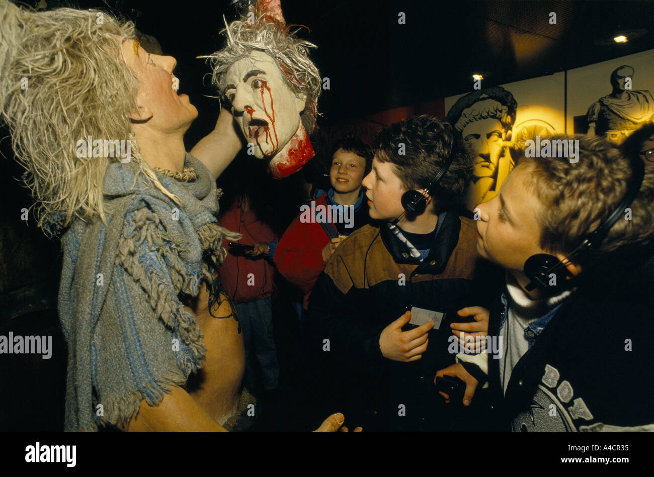 CHILDREN LOOKING AT DISPLAY OF DRUID RITUALS, MAN HOLDING A BLEEDING HEAD. WHITE CLIFFS EXPERIENCE, DOVER, ENGLAND, MARCH 1994 - Stock Image