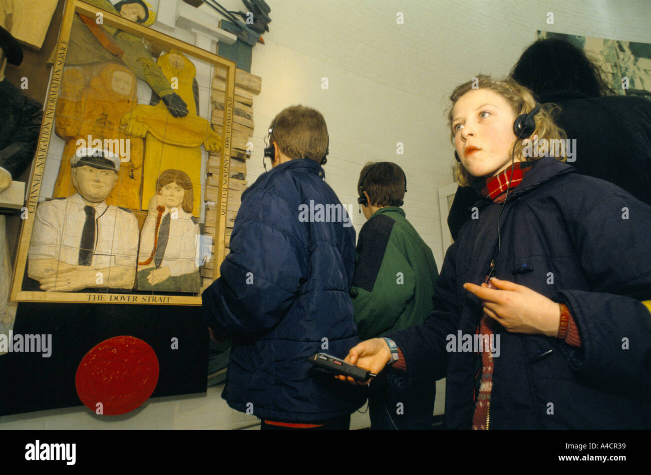 CHILDREN LOOKING AT DISPLAY AT WHITE CLIFFS EXPERIENCE WITH THE HELP OF AUDIIO GUIDE & HEADPHONES. DOVER, ENGLAND, MARCH 1994 - Stock Image