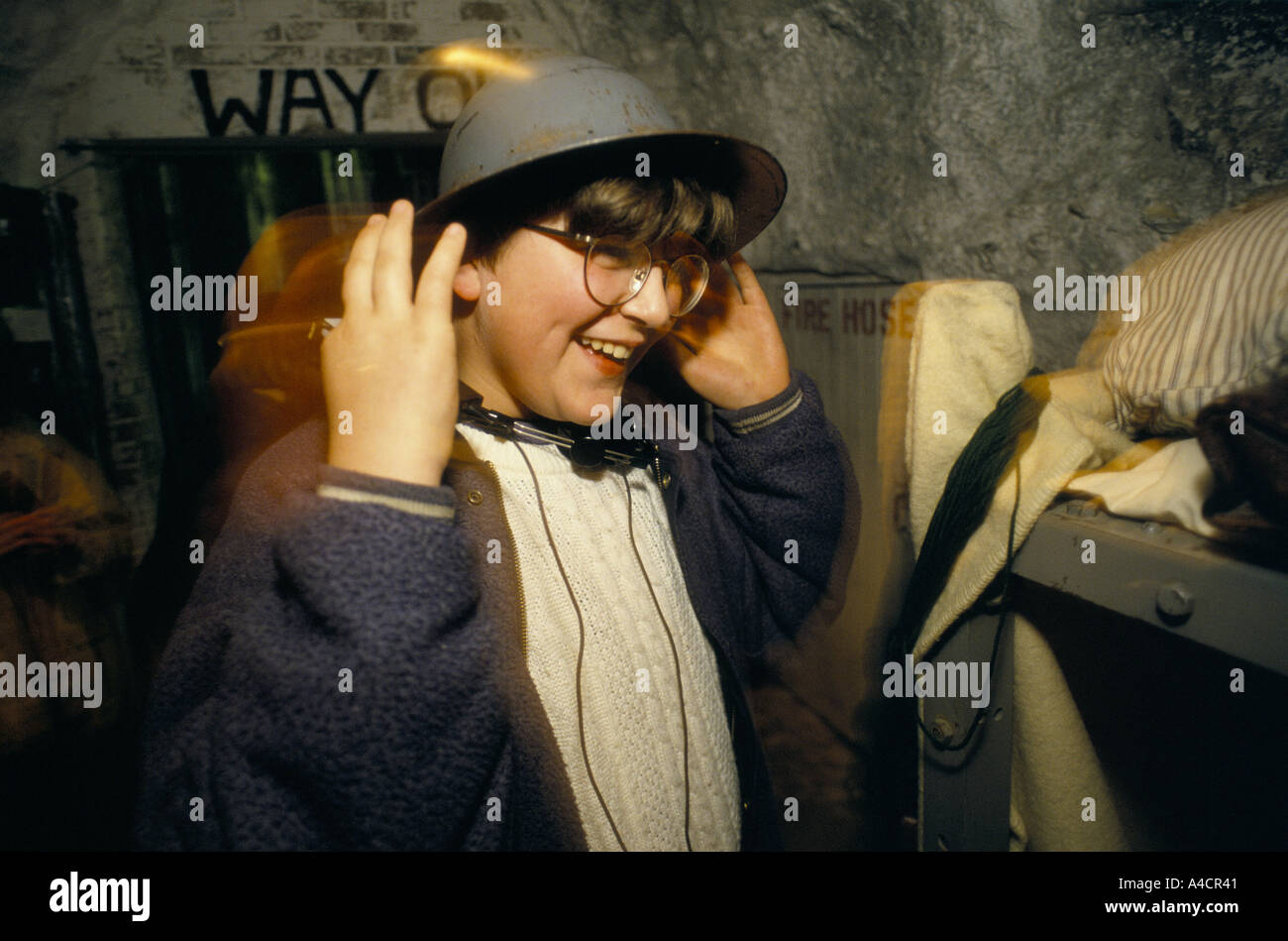 CHILD PUTTING ON A METAL HELMET WORN BY ANTI-AIRCRAFT GUNNER CREWS DEFENDING ENGLAND DURING THE SECOND WORLD WAR AT THE WHITE CL - Stock Image
