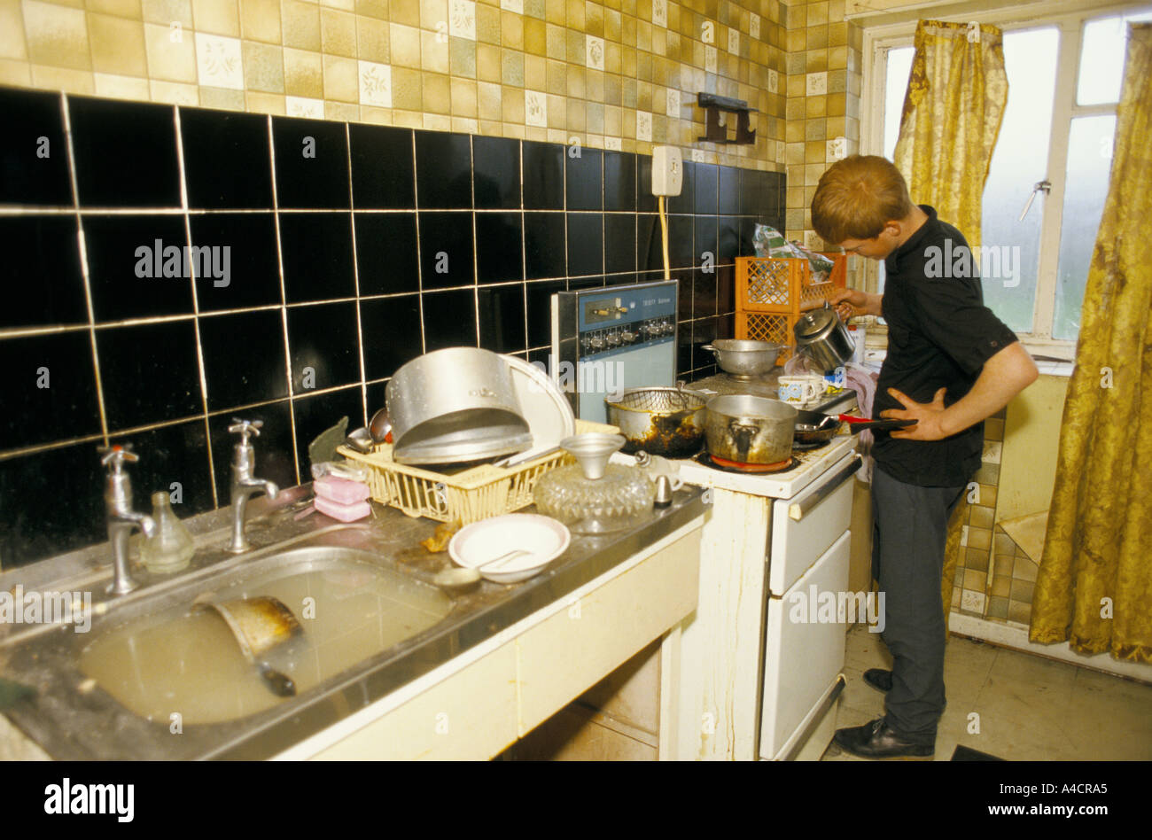 UNEMPLOYED YOUNG MAN MAKES TEA  IN HIS FILTHY KITCHEN WITH A BLOCKED SINK. BOOTLE, LIVERPOOL. ENGLAND - Stock Image
