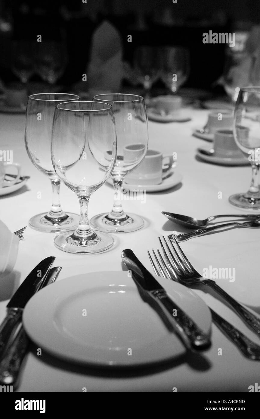 dinner table setting including a knife fork spoon dinner plate and glasses on a white table cloth with upright napkins in black & dinner table setting including a knife fork spoon dinner plate and ...