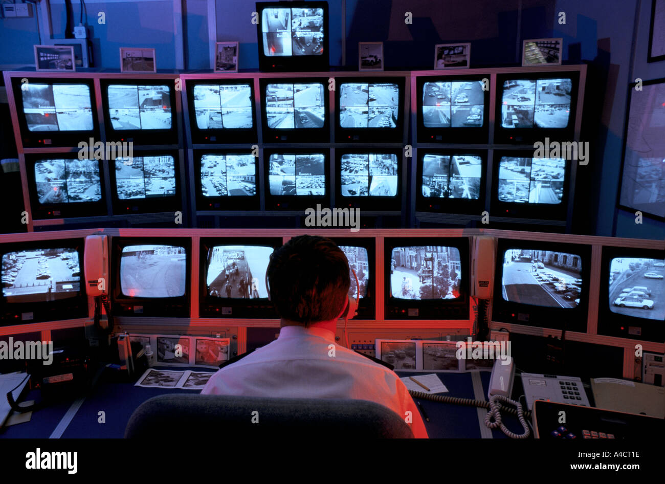 Security officer watching camera feeds from King's Lynn city centre in the town's surveillance centre - Stock Image