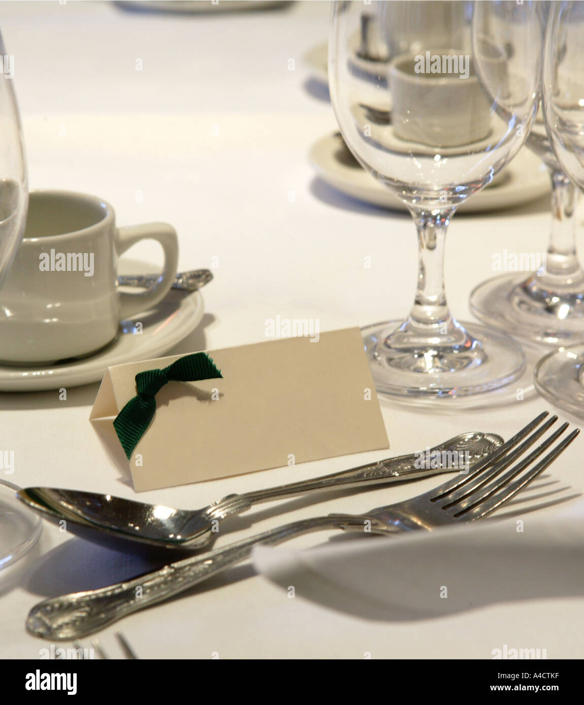 table setting including a blank name card and a knife fork spoon dinner plate and glasses on a white table cloth with upright na & table setting including a blank name card and a knife fork spoon ...