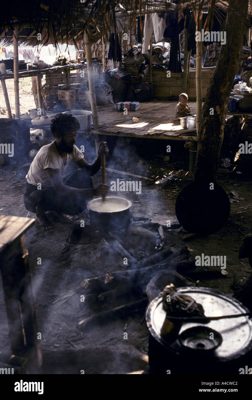 60 Karen muslim families displaced by Burmese army offensives have set up camp at Shou Tah.  A father stirs a cooking pot. - Stock Image