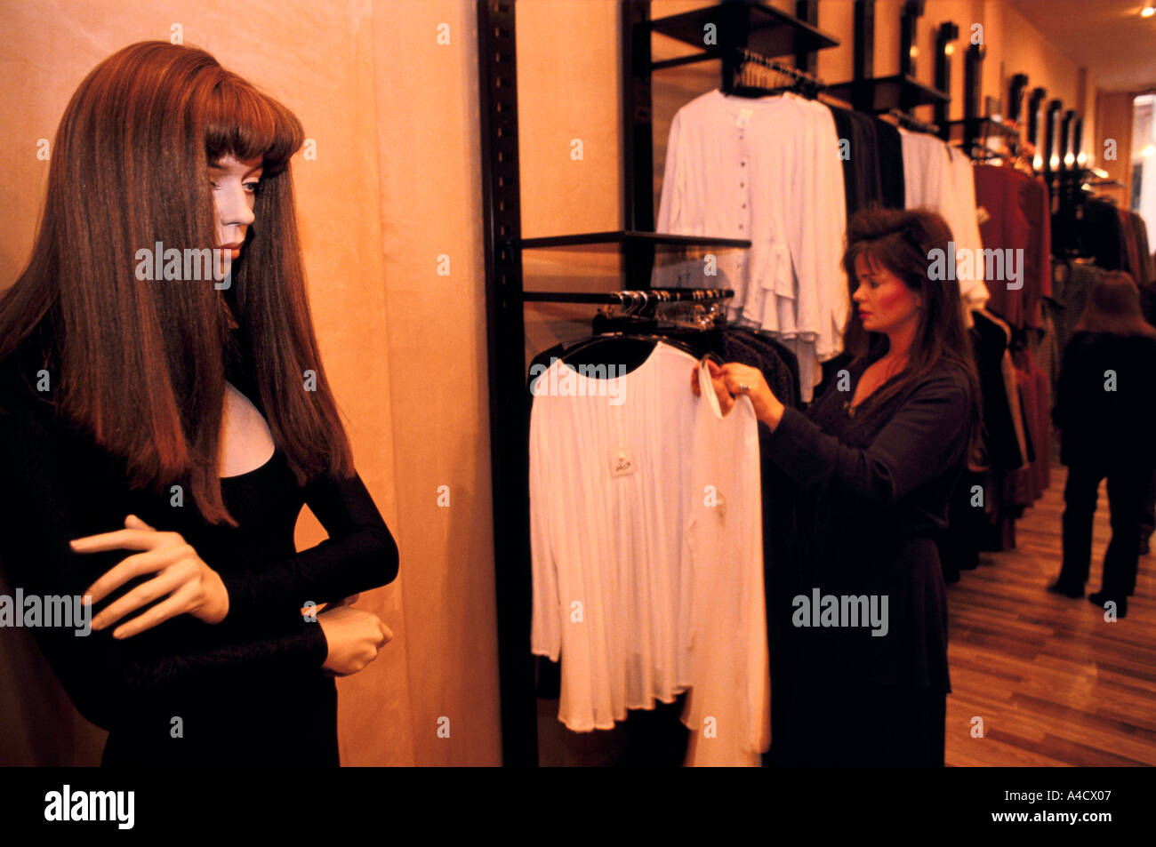 A lifelike manaquin stands in a self-absorbed pose as a women shops in a clothing store at the Lakeside Shopping Centre, Kent - Stock Image