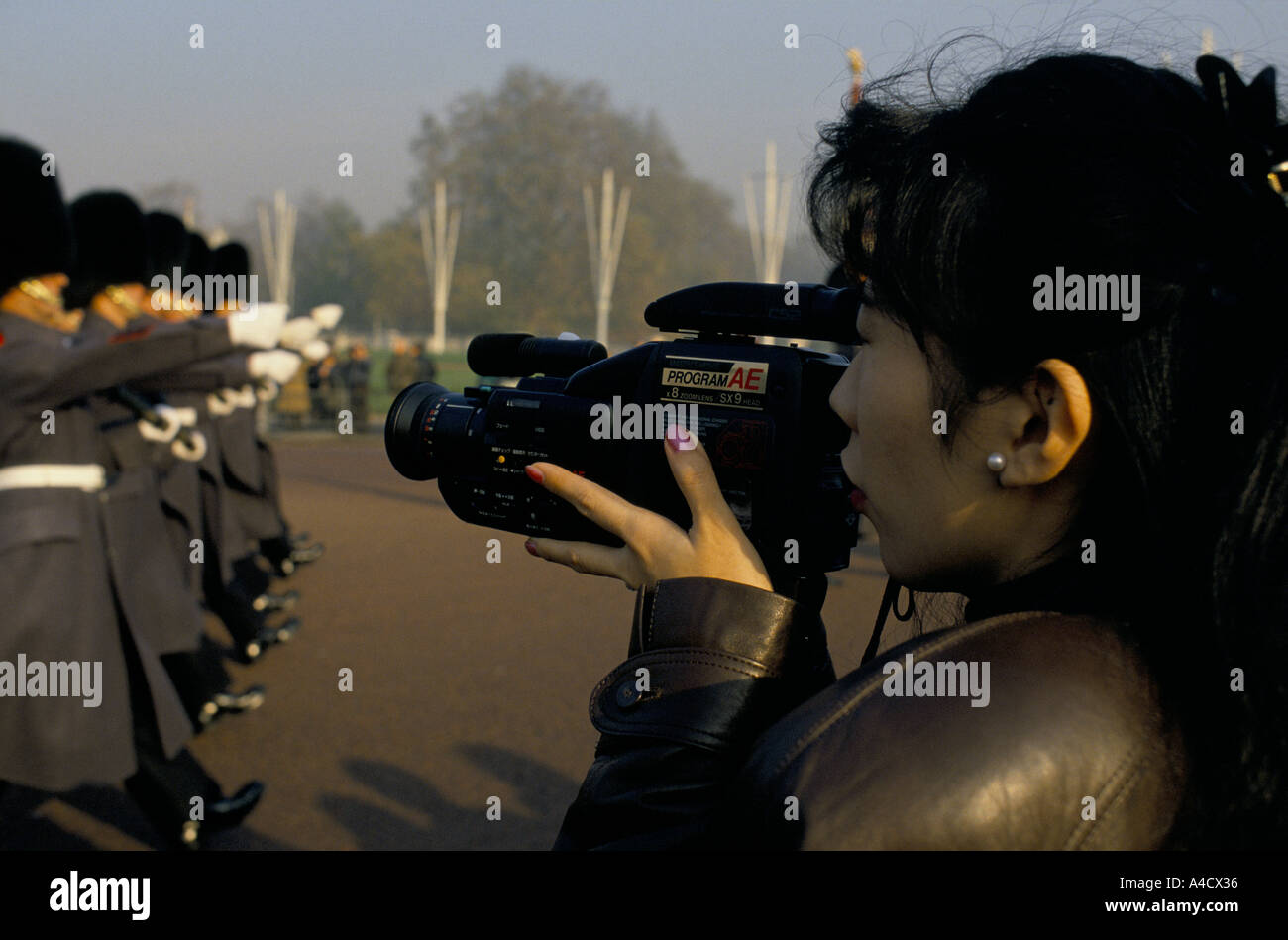 ORIENTAL WOMAN TOURIST FILMING THE ROYAL GUARDSMEN WITH BEARSKIN HAT OUTSIDE BUCKINGHAM PALACE, LONDON - Stock Image