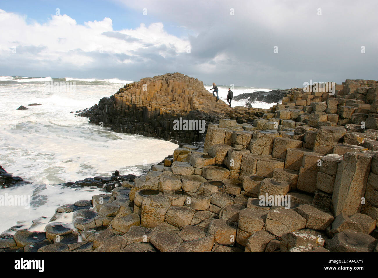 County Antrim Giants Causeway couple climbing on rocks surrounded by heavy surf Stock Photo