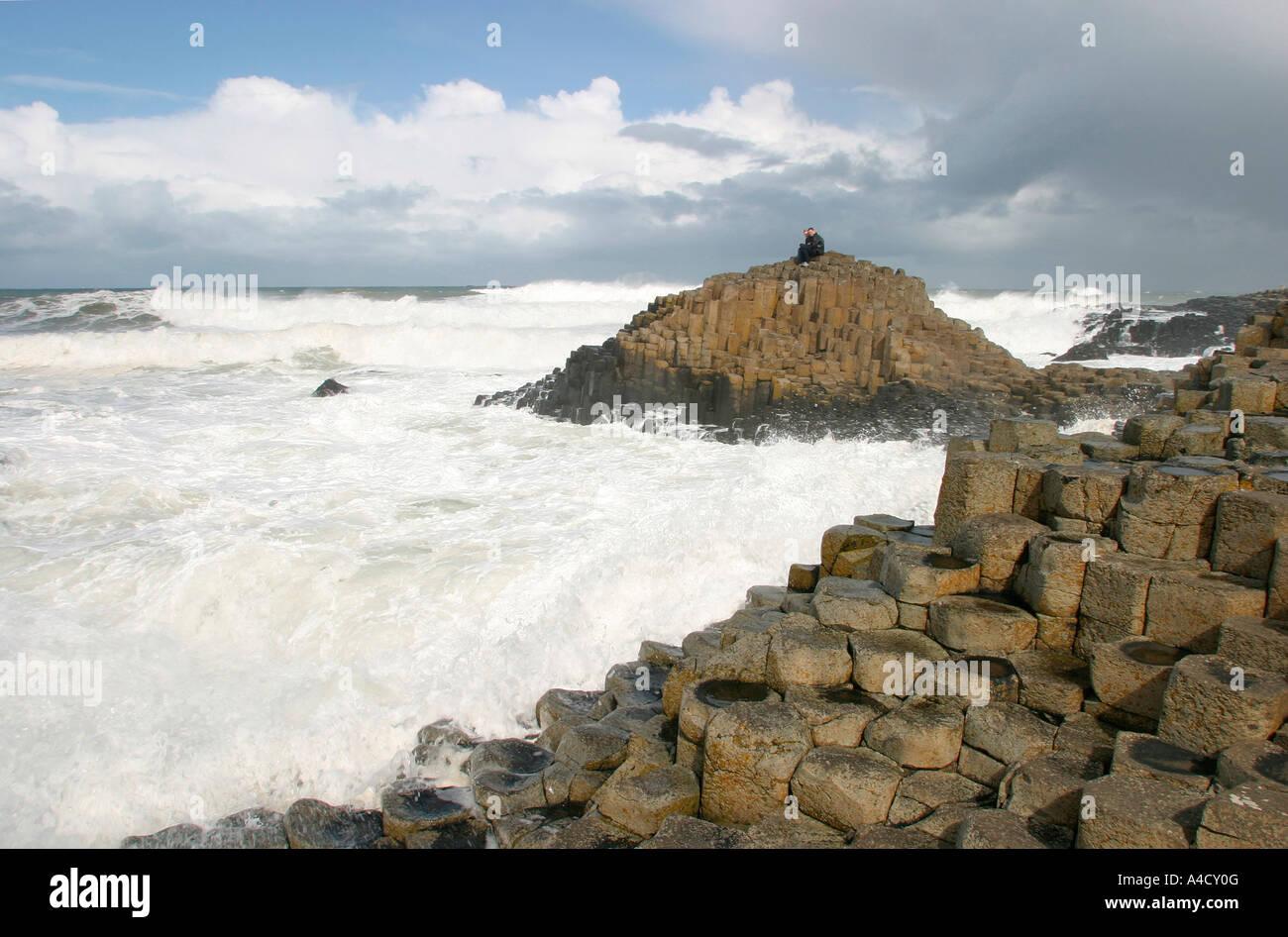 UK County Antrim Giants Causeway couple sat on rocks with waves crashing around Stock Photo