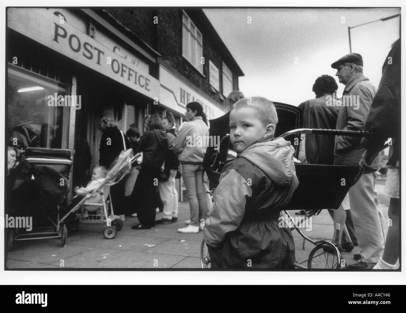 A weekly queue outside the post office of  people  collecting their benefit cheques,  Grangetown  Teeside, UK 1990 - Stock Image