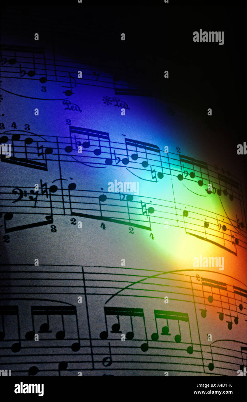 A rainbow of colours cast by a prism, illuminates a page of piano music by Chopin. - Stock Image
