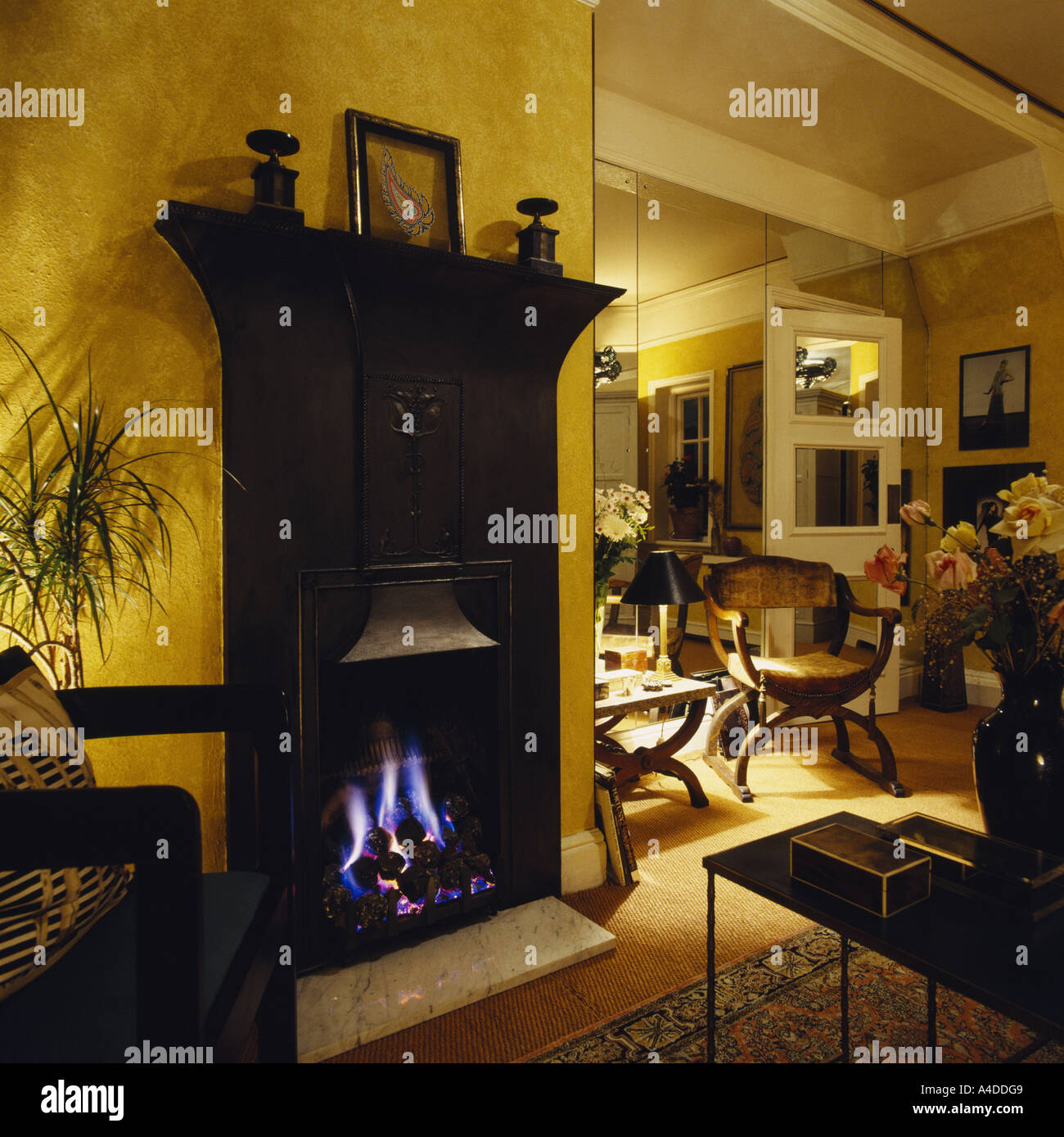 Lighted gas fire in traditional black cast iron fireplace in modern eighties living room Stock Photo